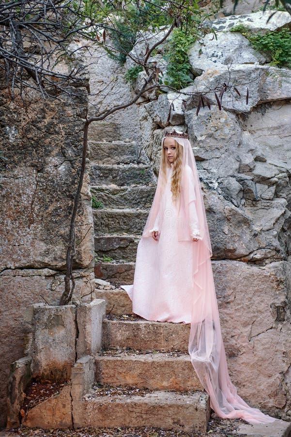 Den unga vita skälmskt naturväxendrottningen i en krona med en skyla och ett långt klär ner stentrappan i ett sagolikt läge royaltyfri fotografi