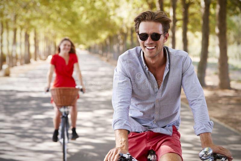 Den unga vita vuxna parridningen cyklar på en tyst solig väg arkivbilder