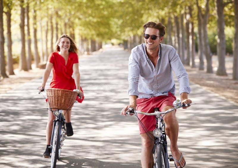 Den unga vita vuxna parridningen cyklar på trädet fodrad väg arkivfoton
