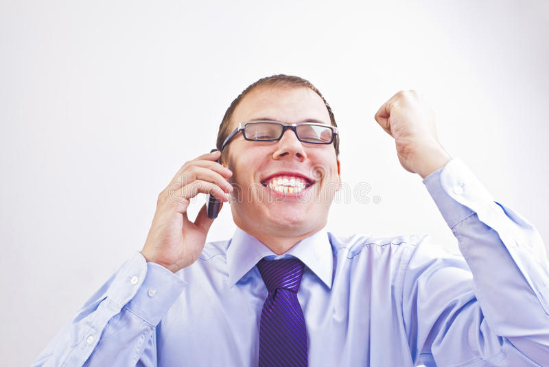 Den unga vuxna affärsmannen reagerar till bra nyheterna som mottas via cellen arkivfoton
