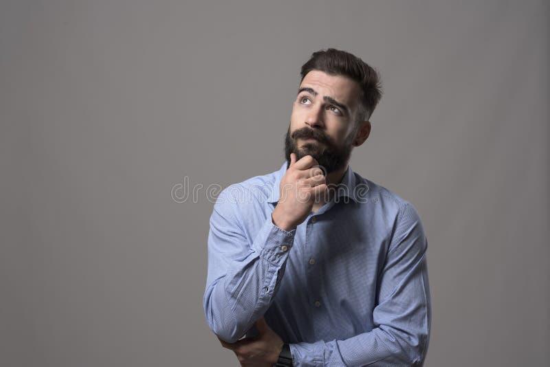 Den unga vuxna hipsteraffärsmannen som tänker och ser upp på copyspace, medan rörande, uppsöker royaltyfria foton