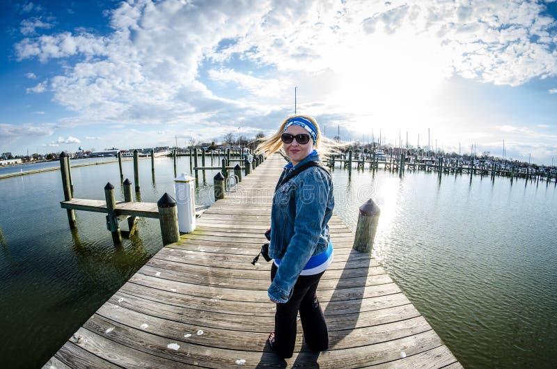Den unga vuxna kvinnan med långt blont hår piskar hennes hår, som hon vänder omkring på en sjösidaskeppsdocka i Maryland royaltyfria bilder