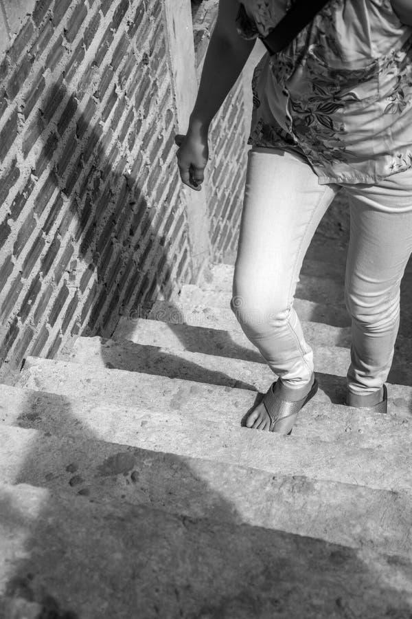 Den unga vuxna kvinnan som går upp trappan, och tegelstenväggen lurar under royaltyfria bilder