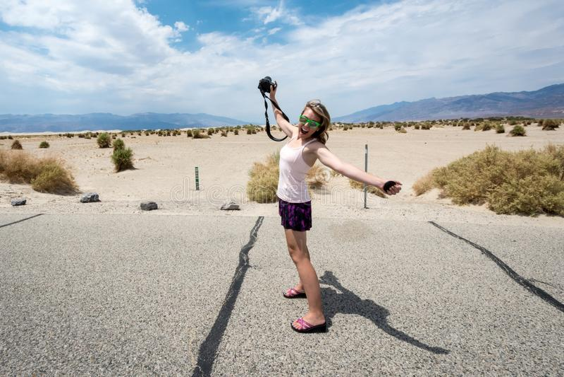 Den unga vuxna kvinnliga fotografen på en vägtur till och med den Death Valley nationalparken, står och sträcker hennes armar och arkivfoto