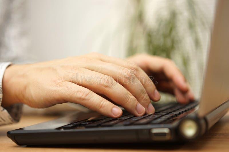 Den unga vuxna människan skriver på bärbar datordatortangentbordet royaltyfri fotografi