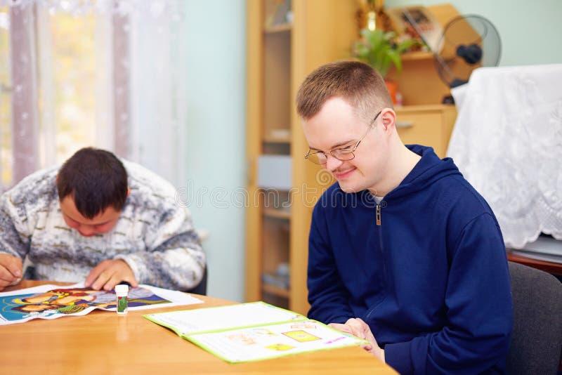 Den unga vuxna mannen kopplar in i självstudien, i rehabiliteringmitt fotografering för bildbyråer