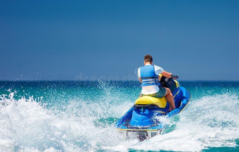 Den unga vuxna mannen som kör vågen på strålen, skidar under sommarsemester royaltyfri fotografi
