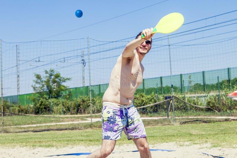 Den unga vuxna mannen spelar tennis på stranden royaltyfria foton