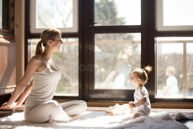 Den unga yogin fostrar och behandla som ett barn dottersammanträde, sund sportig dag royaltyfria foton