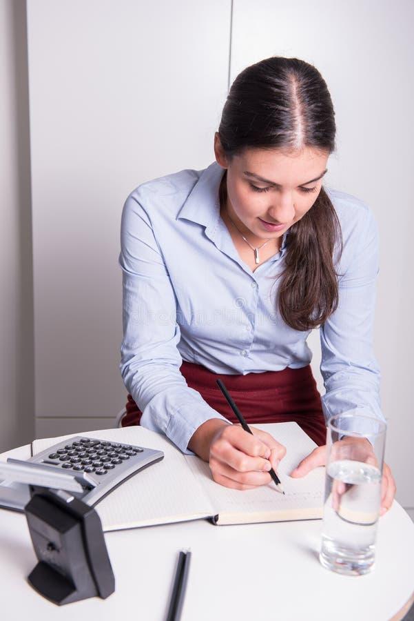 Den unga yrkesmässiga kvinnlign arbetar under tidtryck royaltyfri foto