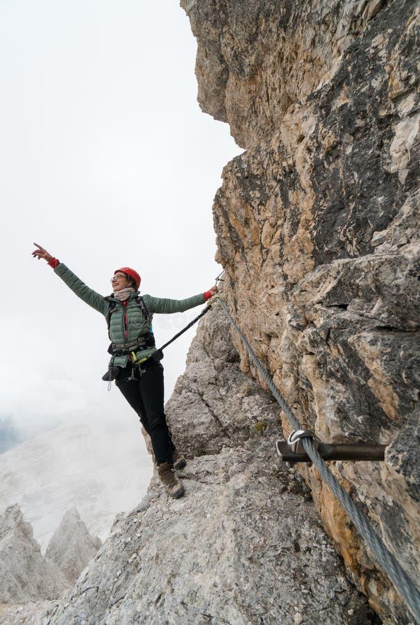 Den ungt kvinnliga klättraren på en lodlinje och utsatt vaggar framsidan som ler och pekar till bergtoppmötet royaltyfri fotografi