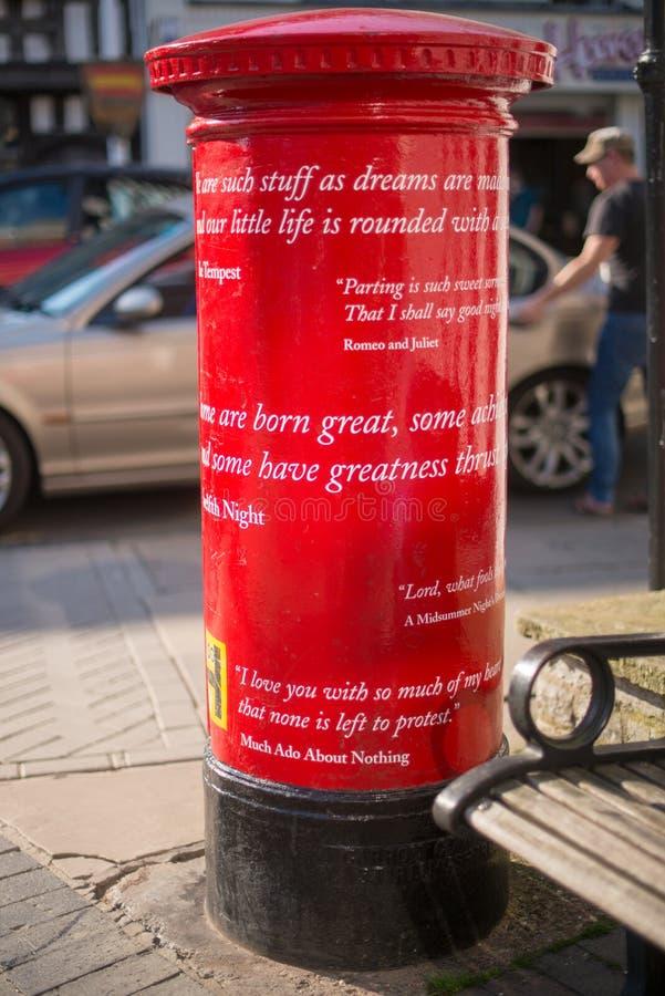 Den unika röda stolpeasken i UK med Shakespeare citerar royaltyfri fotografi
