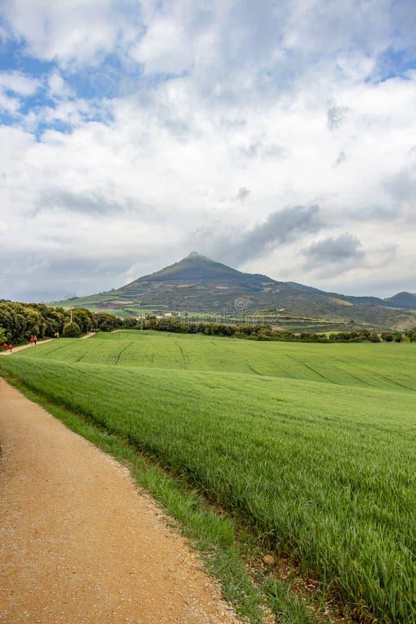 Den Unpaved landsvägen med vallfärdar på Caminoen de Santiago, fördärvar av Castillo de Monjardin i Navarre, Spanien i arkivbild