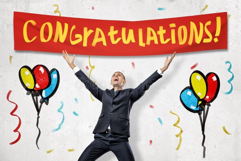 Den upphetsade affärsmannen som firar framgång med det röda 'LYCKÖNSKAN'tecknet över och, målade färgrika ballonger fotografering för bildbyråer