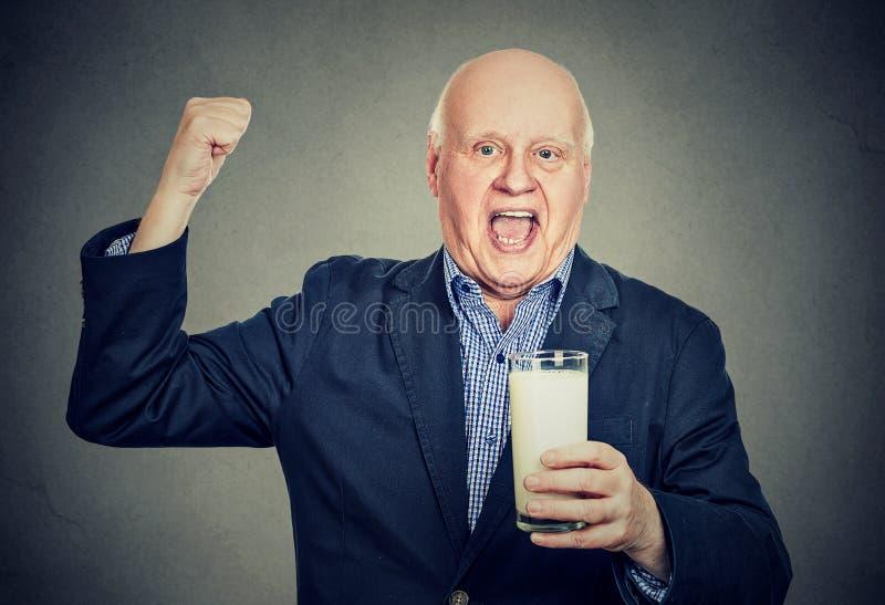 Den upphetsade höga gentlemannen som rymmer ett exponeringsglas av, mjölkar royaltyfria foton