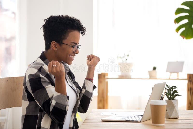 Den upphetsade kvinnan känner lyckligt sammanträde på skrivbordet inomhus arkivfoton