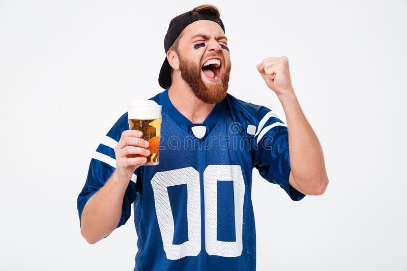 Den upphetsade skrikiga manfanen som dricker öl, gör vinnaren att göra en gest royaltyfri bild