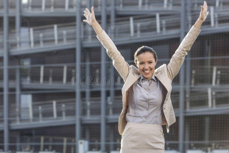 Den upphetsade unga affärskvinnan med armar lyftte anseende mot kontorsbyggnad royaltyfri fotografi