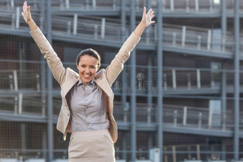 Den upphetsade unga affärskvinnan med armar lyftte anseende mot kontorsbyggnad royaltyfri bild