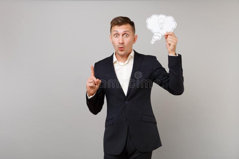Den upphetsade unga affärsmannen i dräktinnehav säger molnet med lightbulben, pekfinger upp med stor ny idé som isoleras på arkivbild