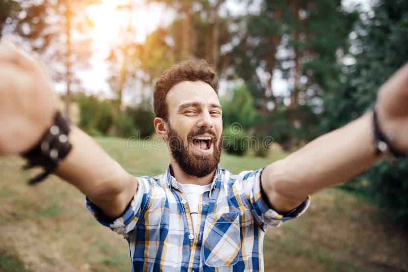 Den upphetsade unga hipstermannen gör selfie i parkera på solnedgången arkivfoto
