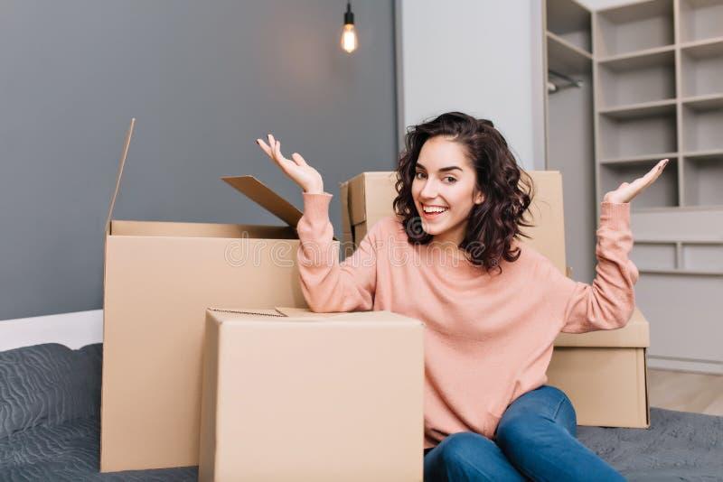 Den upphetsade unga kvinnan på säng omger askar, låda som ler till kameran i modern lägenhet Flytta sig till den nya lägenheten s royaltyfri bild