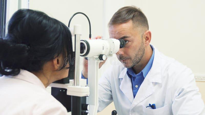 Den uppmärksamma ögonläkaren undersöker ögonen av hans patient royaltyfri fotografi