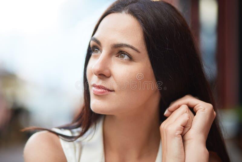 Den uppmärksamma fokuserade unga kvinnan för brunetten med angenämt utseende, mörkt hår, blickar pensively åt sidan, beskådar om  fotografering för bildbyråer