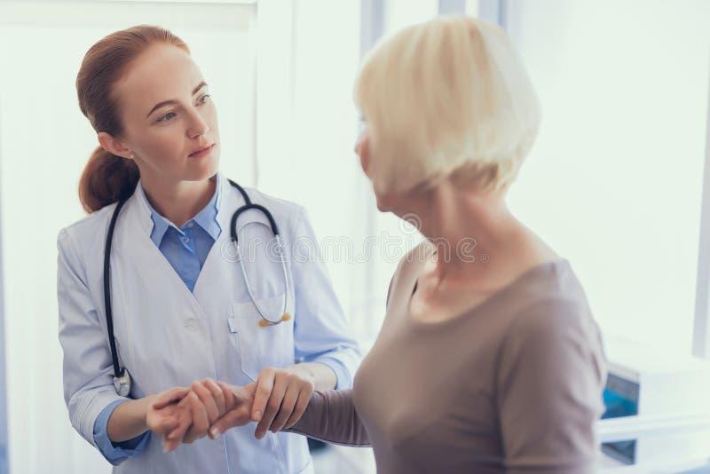 Den uppmärksamma läkaren lyssnar till kvinnaklagomål royaltyfri foto