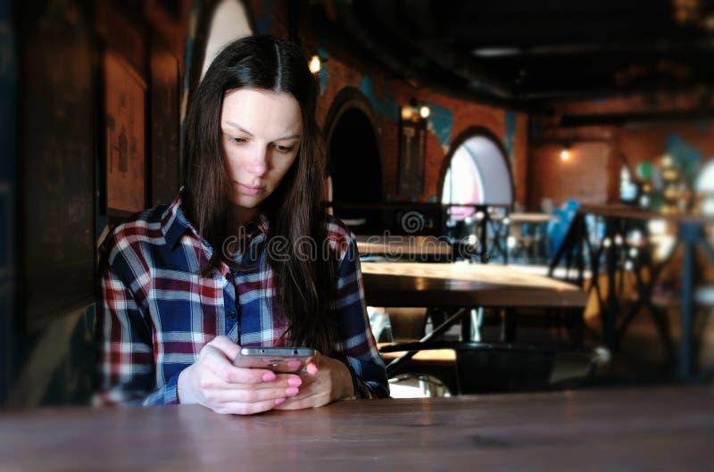 Den upprivna kvinnan överför ett meddelande i telefonsammanträdet i ett kafé Iklätt en plädskjorta royaltyfri fotografi