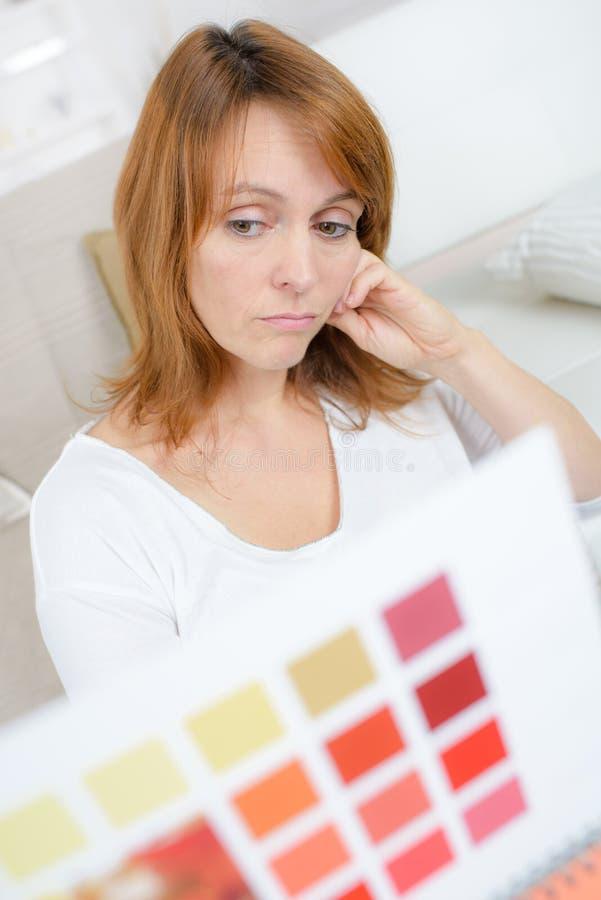 Den upprivna kvinnan gillar inte färg från provkartaboken royaltyfri bild