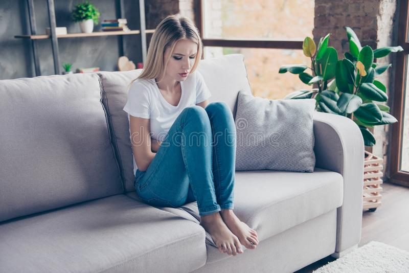 Den upprivna kvinnan har första tecken av pms Hon sitter på en soffa arkivbilder
