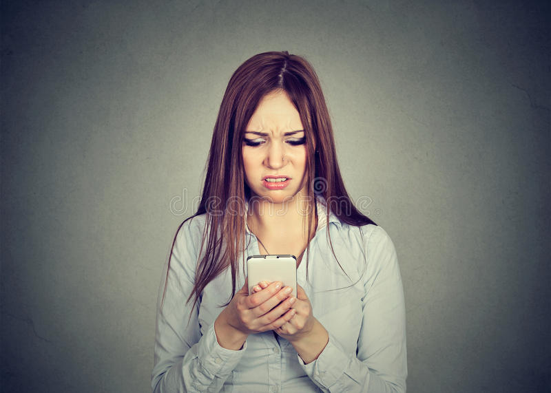 Den upprivna kvinnan som ser mobiltelefonen, misshog med meddelandet som hon mottog royaltyfri bild