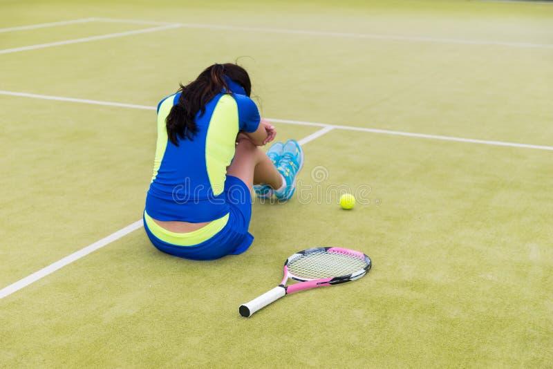 Den upprivna kvinnliga tennisspelaren sitter på domstolen royaltyfria foton