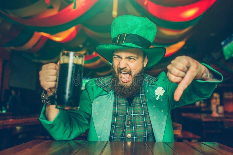 Den upprivna och disgussed unga mannen i grön dräkt poserar på kamera Han sitter på tabellen i bar och stor tumme för show ner Gr royaltyfri fotografi