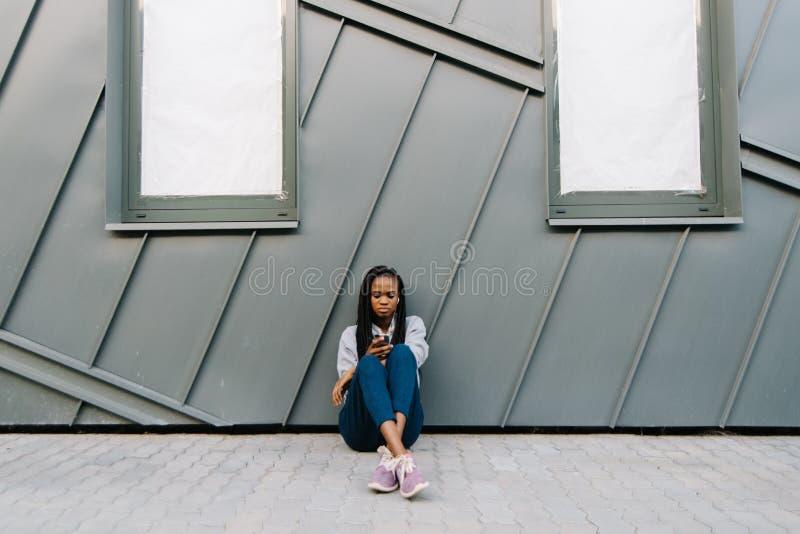 Den upprivna säkra afrikanska kvinnan är smsa och bläddra nolla-nt honom mobiltelefonen, medan sitta på jordningen och benägenhet arkivbild