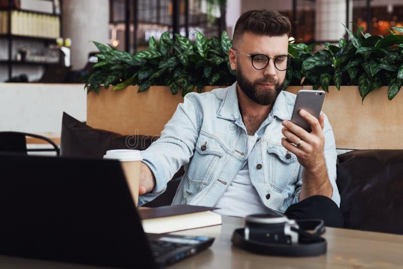 Den uppsökte hipstermannen i exponeringsglas sitter i kafé på tabellen, arbeten på bärbara datorn, brukssmartphone På tabellen är arkivfoton