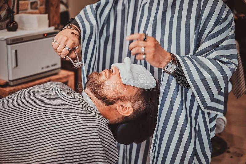 Den uppsökte klienten fick precis bra beardcare från moderiktig barberare royaltyfria foton