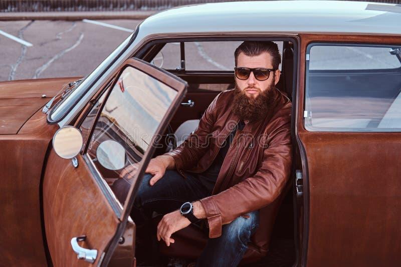 Den uppsökte mannen i iklätt brunt läderomslag för solglasögon sitter bak hjulet av en stämd retro bil med den öppna dörren fotografering för bildbyråer