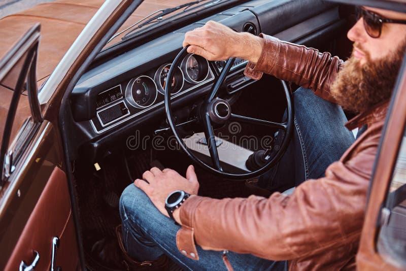 Den uppsökte mannen i iklätt brunt läderomslag för solglasögon sitter bak hjulet av en stämd retro bil med den öppna dörren royaltyfria bilder