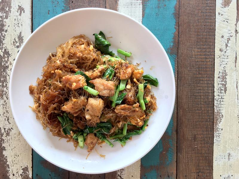 Den uppståndelse stekte plana risnudeln med soya och griskött i den vita maträtten på den färgglade trätabellen i thai kallat `-b royaltyfri bild