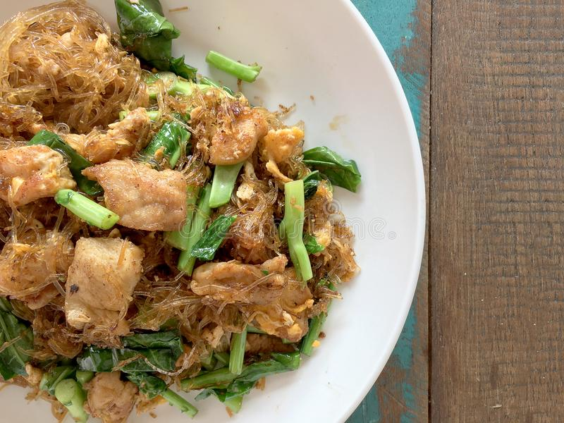 Den uppståndelse stekte plana risnudeln med soya och griskött i den vita maträtten på den färgglade trätabellen i thai kallat `-b arkivbild
