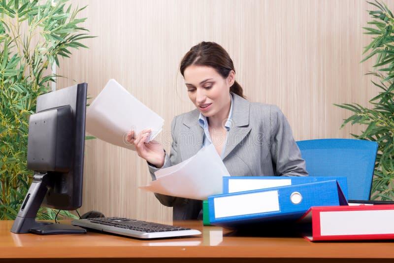 Den upptagna affärskvinnan i kontoret under spänning royaltyfria bilder
