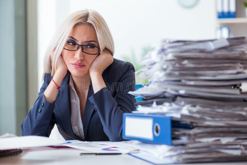 Den upptagna affärskvinnan som i regeringsställning arbetar på skrivbordet fotografering för bildbyråer