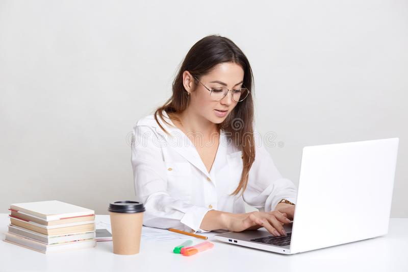 Den upptagna freelanceren mottar emailen, skriver återkoppling på bärbar datordatoren, bär runda exponeringsglas, den iklädda vit royaltyfria bilder