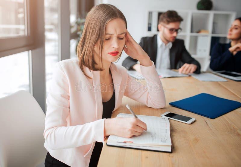 Den upptagna fundersamma unga kvinnan sitter på tabellen i rum och handstil i anteckningsbok Hennes kollegor arbetar bakom Hon är arkivbild