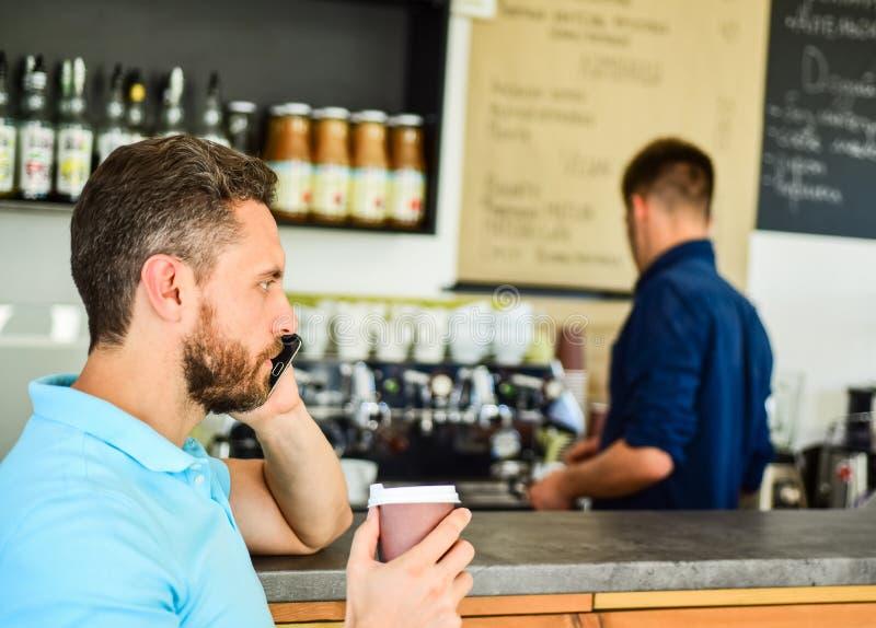 Den upptagna grabben talar telefonen, medan koppla av kaffeavbrottet Ordna till för att höra dig Manhållkopp av drinken, medan ha royaltyfri fotografi