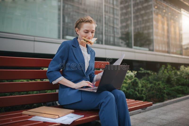 Den upptagna kvinnan är bråttom, henne har inte tid, henne ska äta mellanmålet utomhus Arbetare som äter och arbetar med royaltyfri foto