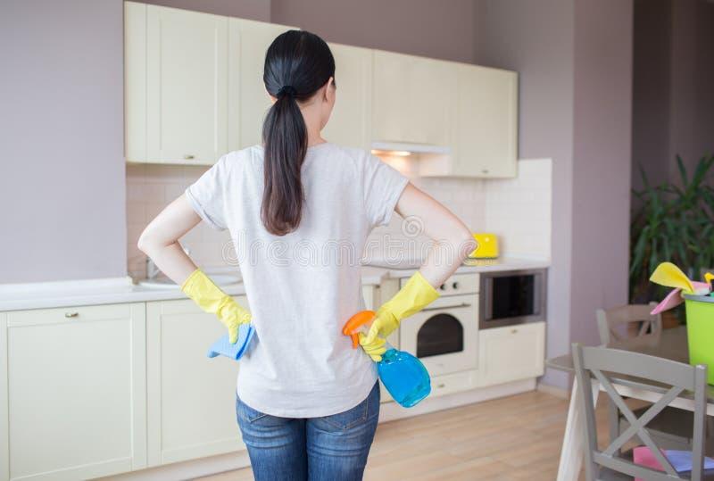 Den upptagna kvinnan står i kök och ser möblemang Hon bär gula handskar Flickan har blåttsprej i en hand och trasa in royaltyfri foto