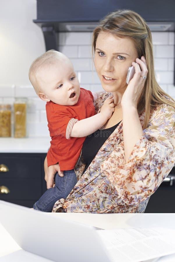 Den upptagna modern med behandla som ett barn att klara av med den hemmastadda stressiga dagen royaltyfri fotografi
